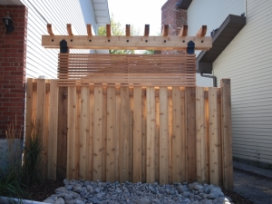 """We constructed a """"Custom Cedar Arbor"""" at our """"Rhatigan Ridge"""" landscape revitalization project in order to hide the back of the shed that sat just behind the fence and was visible from the road in front"""