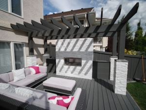 """This landscape revitalization project in Leger included an amazing """"Composite Deck & Pergola"""" with a cozy """"Gas Fireplace"""""""