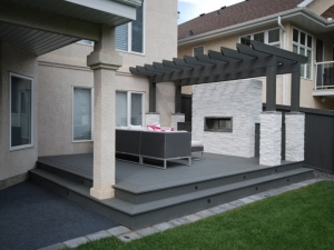 """This """"Composite"""" Deck was constructed in order to add more """"OutdoorSpace"""" for our clients to enjoy and entertain. We incorporated a """"Pergola"""" for added privacy and a unique """"Natural Stone Feature Wall"""" with """"Built-In Gas Fireplace"""""""