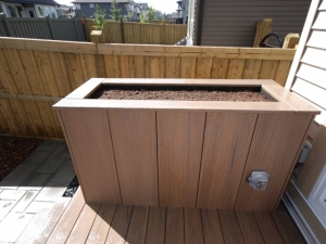 """This custom built Planter was constructed out of pressure treated lumber and faced with """"Composite"""" boards. It also included a built-in Drainage System in order to control the moisture of the soil. It also provided a great place to mount the power outlet for the water fountain"""
