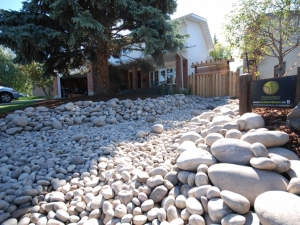"""The incorporation of a """"Dry River Bed"""" really enhanced the curb appeal of this landscape revitalization project in """"Rhatigan Ridge"""""""