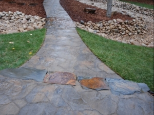 """We incorporated a Dry River Bed utilizing """"Athabasca River Rock"""" and a winding sidewalk constructed out of """"Mega-Libre (Victorian) Slab"""" by Belgard. We installed a Natural Stone Patio at the front entrance to this Hastings Lake property and we tied that in with a series of Natural Stone bridge crossings in order to maintain the """"natural"""" look of this lake property"""