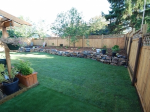"""On this Blue Quill project we incorporated a Natural Stone (Kendall) Retaining Wall in order to transform this sloped and otherwise """"dysfunctional"""" back yard"""