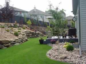 """The design and construction of a """"Natural (Sand Stone) Retaining Wall"""" assisted in creating more """"usable"""" space in the back yard of this """"Citadel at Magrath"""" property"""