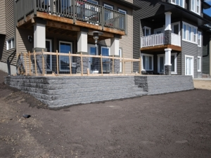 "A ""PISA 2 Retaining Wall System"" c/w ""Built-In (dimensional) Steps"" helped to reduce the severe slope at this otherwise ""dysfunctional"" walkout lot"